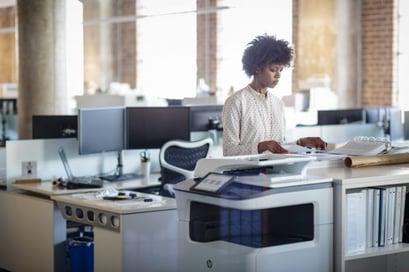 Une femme au bureau à l'aide d'un HP PageWide Managed P77750z-2