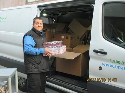 smartprint employee loading shoeboxes into van for the shoebox project