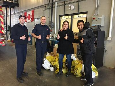 smartprint team members at the firehall with grocery bags for the winter food drive