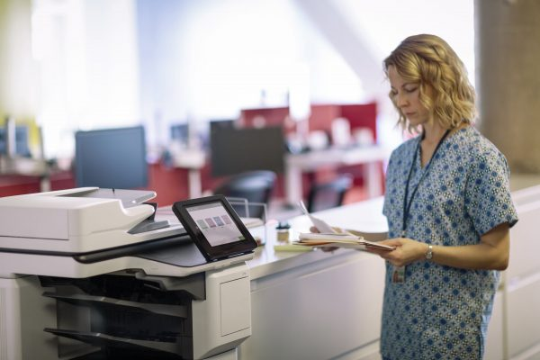 nurse standing by an hp mfp in an optimized healthcare print environment